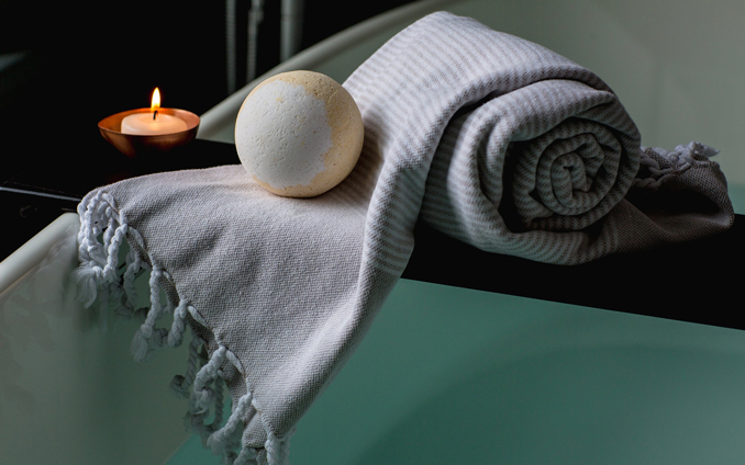 Towel on edge of bath with bathbomb and candle